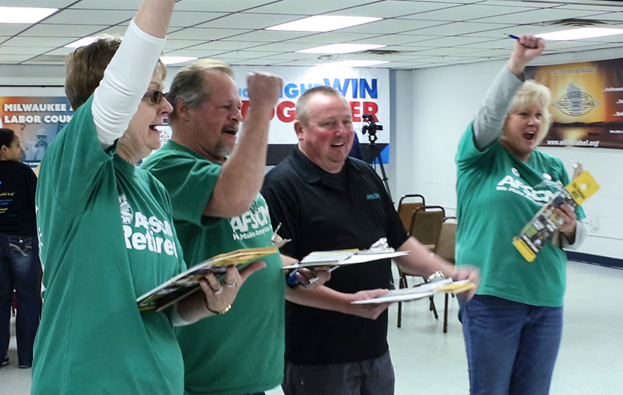 Photograph of two women and two men cheering - presumably for their winning candidate - and all of whom are wearing AFSCME shirts.