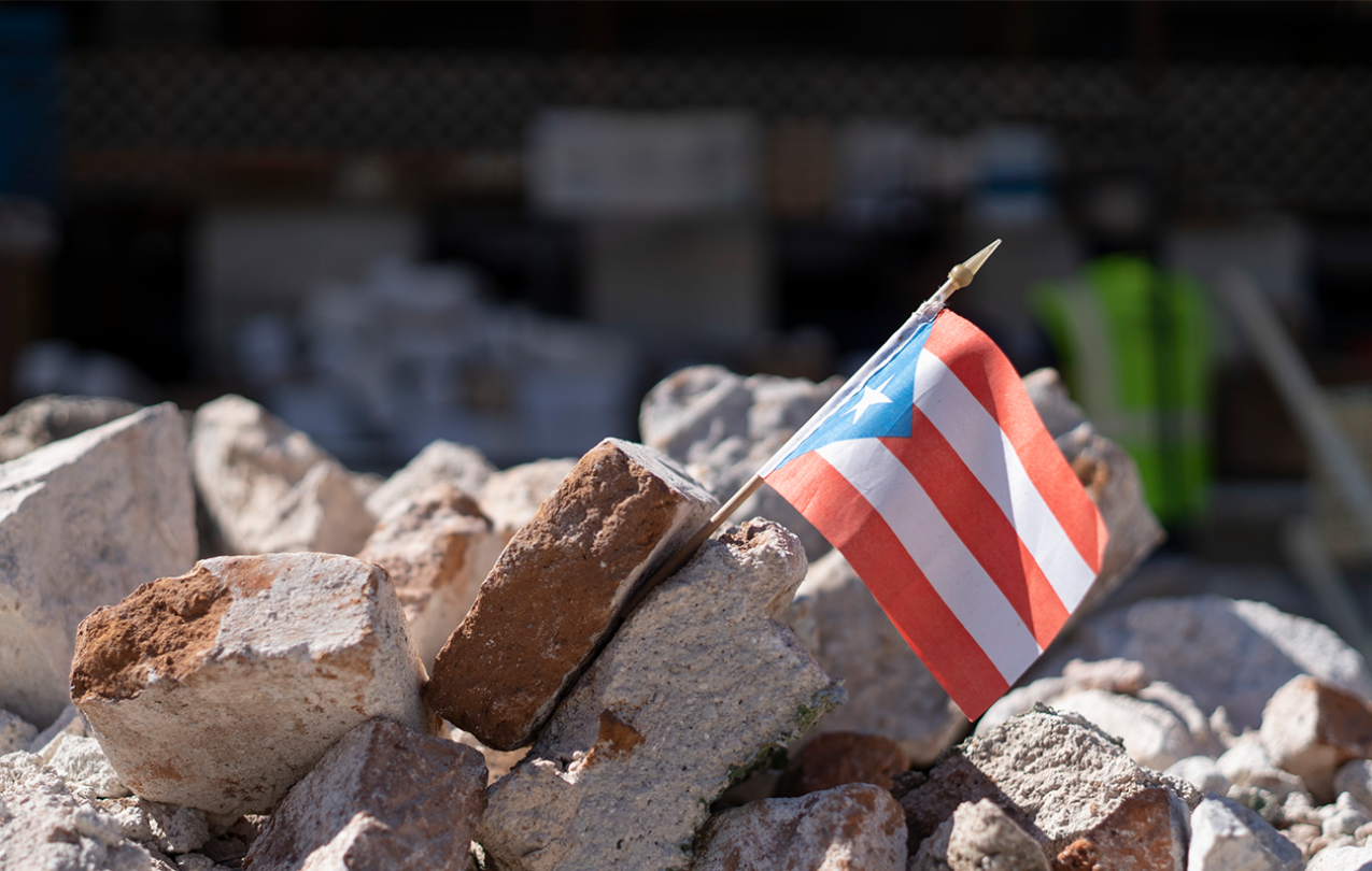 A Puerto Rican flag sits between stone rubble.